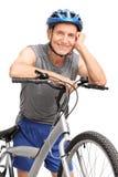 Aîné dans les vêtements de sport se penchant sur une bicyclette Images libres de droits
