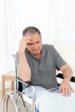 Aîné dans son fauteuil roulant ayant un mal de tête Photographie stock