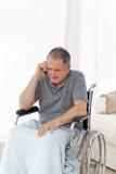 Aîné dans son téléphoner de fauteuil roulant Photos libres de droits