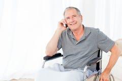 Aîné dans son téléphoner de fauteuil roulant Photo libre de droits
