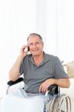 Aîné dans son téléphoner de fauteuil roulant Image libre de droits