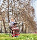 Aîné dans un fauteuil roulant lisant un livre en parc Photos libres de droits