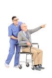 Aîné dans un fauteuil roulant se dirigeant avec le doigt Image stock