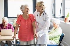 Aîné de aide d'infirmière à l'aide de marche Image libre de droits