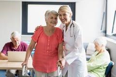 Aîné de aide d'infirmière à l'aide de marche Image stock