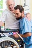 Aîné de aide d'infirmière pluse âgé de soin de lit au fauteuil roulant Images libres de droits