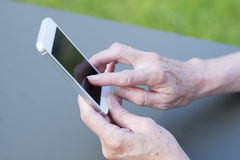 Aîné de femme à l'aide d'un téléphone portable dans le jardin Photo libre de droits
