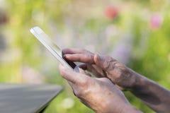 Aîné de femme à l'aide d'un téléphone portable dans le jardin Photos libres de droits