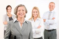 Aîné de femme d'affaires avec des collègues dans le dos Image libre de droits