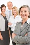 Aîné de femme d'affaires avec des collègues dans le dos Image stock