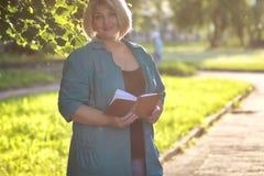 Aîné de femme en parc avec le livre Photographie stock libre de droits