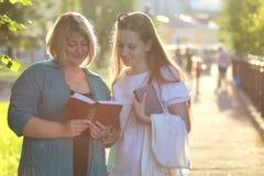 Aîné de femme en parc avec le livre Photos libres de droits