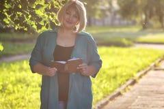 Aîné de femme en parc avec le livre Photo stock