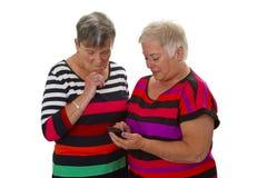 Aîné deux féminin avec le téléphone portable Image libre de droits