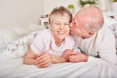 Aîné embrassant son épouse dans le lit Photographie stock libre de droits