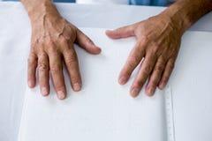Aîné employant Braille pour lire Image stock