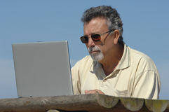 Aîné en stationnement avec un ordinateur Images libres de droits