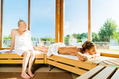 Aîné et jeune femme dans la transpiration de sauna Image libre de droits