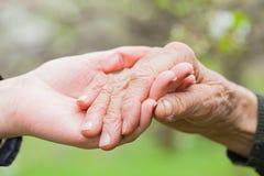 Aîné et jeune femme tenant des mains Image stock