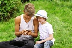 Aîné et jeune frère regardant au smartphone Image stock