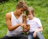 Aîné et jeune frère regardant au smartphone Photographie stock