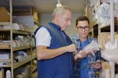 Aîné et jeune homme recherchant l'article dans l'entrepôt Photo stock