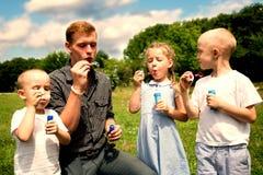 Aîné et jeunes frères soufflant des bulles de savon Images libres de droits