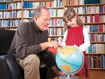Aîné et petite-fille regardant un globe Photos libres de droits