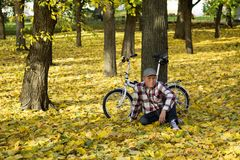 Aîné et sa bicyclette en parc d'automne Image stock