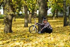 Aîné et sa bicyclette en parc d'automne Photos stock