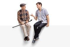 Aîné et un jeune homme s'asseyant sur un panneau et parler Photos stock