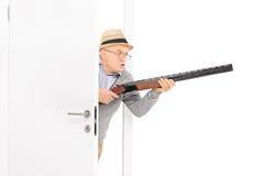 Aîné fâché avec un fusil marchant par une porte Photo stock