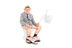 Aîné fâché ondulant un drapeau blanc posé sur la toilette Image libre de droits