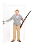 Aîné fâché tenant un fusil de chasse et marchant par une porte Photographie stock libre de droits