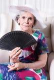 Aîné féminin actif avec la fan dans sa main Images libres de droits
