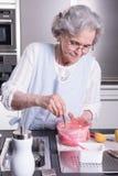 Aîné féminin actif dans la cuisine Photos libres de droits