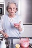 Aîné féminin actif dans la cuisine Image libre de droits