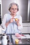 Aîné féminin actif dans la cuisine Images stock