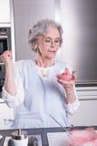 Aîné féminin actif dans la cuisine Photos stock