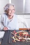 Aîné féminin actif dans la cuisine Image stock