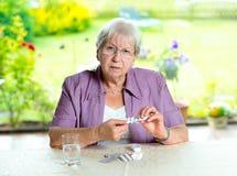 Aîné féminin avec du beaucoup de médicament Photo libre de droits