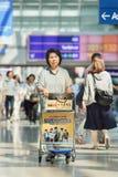 Aîné féminin avec le chariot à bagages à l'aéroport d'Incheon, Corée du Sud Photos stock