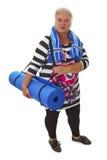 Aîné féminin avec le tapis bleu de gymnase Image stock