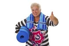 Aîné féminin avec le tapis bleu de gymnase Photographie stock