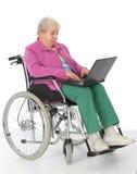 Aîné féminin dans le fauteuil roulant avec l'ordinateur Images stock
