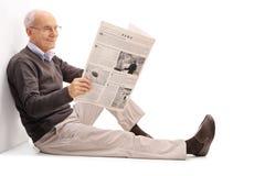 Aîné gai lisant un journal Photographie stock