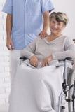 Aîné gai sur le fauteuil roulant avec l'infirmière Photo libre de droits