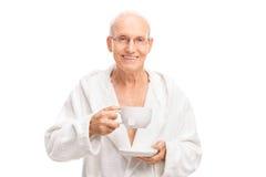 Aîné gai tenant une tasse de thé Photos libres de droits