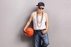 Aîné grincheux dans un équipement de hip-hop tenant un basket-ball Images libres de droits