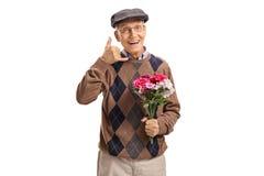 Aîné heureux avec des fleurs me faisant à un appel geste Images libres de droits
